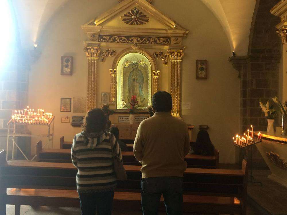 Inside the church Prayers in front of the icon of Madonna de Guadalupe Cusco Peru